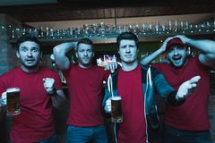 Sports fans shouting sad in front of tv drinking beer at sports bar. They are supporting red team royalty free stock images