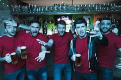 Sports fans shouting sad in front of tv drinking beer at sports bar. They are supporting red team royalty free stock photography