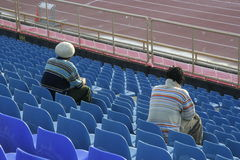 Sports fans in stadium seats. A view of two spectators or sports fans sitting in stadium seats at an athletic field royalty free stock photo