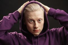 Sports fashion concept. Albino guy posing in sporty clothing over black background. Sports fashion concept. Athlete with blonde hair adjusting hood over the royalty free stock photography