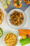 Sports feast - chicken wings, vegetable, french fries, pizza Stock Photo