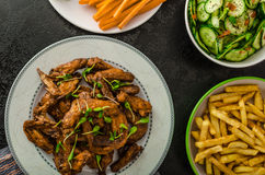Sports feast - chicken wings, vegetable, french fries, pizza Stock Images