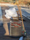 Sports field construction site near. View from the public area through a fence to a sports field construction site with a water barrel with tools in the morning stock photo