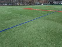 Sports field with no players, red and green lines. Sports play area for soccer and baseball. Bright green artifical turf. Open empty, absent athletes. Urban stock image