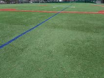 Sports field with no players, red and green lines. Sports play area for soccer and baseball. Bright green artifical turf. Open empty, absent athletes royalty free stock photos
