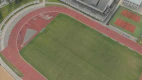 People run in the red stadium fitness. Sports field and red stadium, running, flying on a drone 4k stock video footage