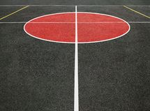 Sports field with white lines. Perspective view of center circle of sports field with white lines. Black and red playing ground for games royalty free stock photography