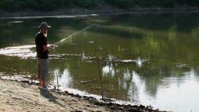 Sports fisherman fishing on lake, using fishing lures; stock footage