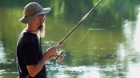 Sports fisherman fishing on lake, using fishing lures; stock video