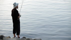 Sports fisherman fishing on river, using fishing lures; stock video footage