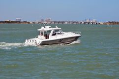 Sports Fishing Boat Powered by Four Outboard Engines. A sport fishing boat powered by four out board engines cruising the florida intra-coastal in the background Royalty Free Stock Photos
