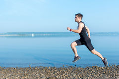 Sports, Fitness. Fit man running workout jogging at beach. Outdoors training. Sports, Fitness. Fit man running workout jogging at beach. Outdoors training Royalty Free Stock Images