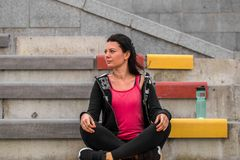 Sporty girl sitting on the stairs. Sports fitness girl sitting on the stairs, the concept of fitness and sports healthy lifestyle Royalty Free Stock Photos