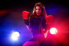 Sports fitness girl wearing boxer mitt in gym. Royalty Free Stock Images