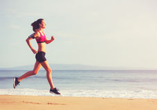 Sports Fitness Woman Running on the Beach at Sunset Stock Images