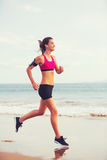 Sports Fitness Woman Running on the Beach at Sunset Royalty Free Stock Image