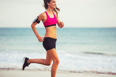 Sports Fitness Woman Running on the Beach at Sunset Royalty Free Stock Images