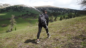 Sports girl with a backpack in a walking walk along the green mountain meadows. in the mountains stock video
