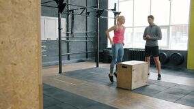 Sports girl busy with crossfit training jumping on wooden box working with coach