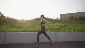 Young woman running on urban area. Sports girl in dark tracksuit performs cardio workout on urban area, tracking shot. Female athlete runs in an urban stock video footage