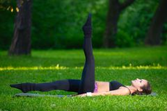 Sports girl does exercises workout outdoors in park Stock Photos