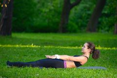 Sports girl does exercises workout outdoors in park Stock Images