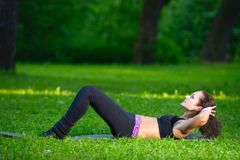 Sports girl does exercises workout outdoors in park Royalty Free Stock Image