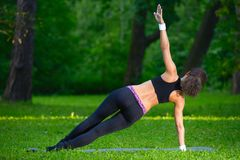 Sports girl does exercises workout outdoors in park Stock Image