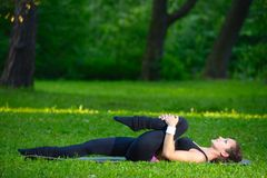 Sports girl does exercises workout outdoors in park Royalty Free Stock Photography
