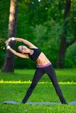 Sports girl does exercises workout outdoors in park Royalty Free Stock Photo