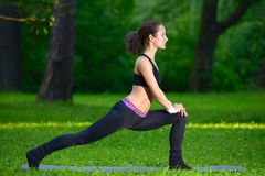 Sports girl does exercises workout outdoors in park Stock Photography