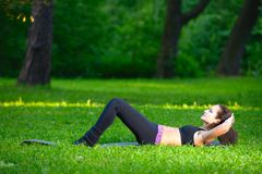 Sports girl does exercises workout outdoors in park Royalty Free Stock Photos