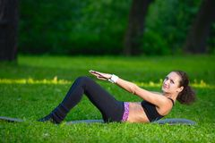 Sports girl does exercises workout outdoors in park Stock Photo