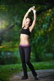 Sports girl does exercises workout outdoors in park Royalty Free Stock Images