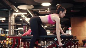 Sports girl doing exercises with dumbbells in the gym. girl in sportswear doing triceps exercises. side view stock video