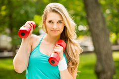 Sports girl exercise with  dumbbells in the park Stock Photo