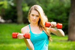 Sports girl exercise with  dumbbells in the park Stock Photography