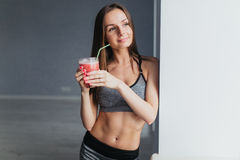 Sports girl after exercise relaxes in a bright room and cocktail drinks Royalty Free Stock Photos