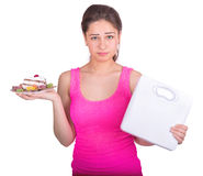Sports girl holding a cake and weight Stock Photos