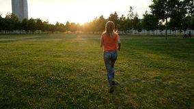 Sports girl jogging through the grass at sunset in a city park, slow motion stock video footage