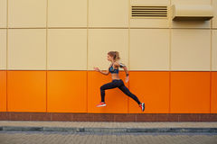 The sports girl jumped on an orange background. Stock Photos