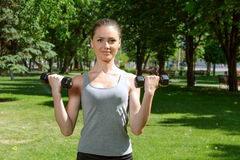 Sports girl makes exercises with dumbbells Royalty Free Stock Image