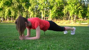 Sports girl makes plank exercise on the lawn stock footage