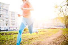 Sports girl on morning run. In park on background of houses. Sunflare effect stock photos