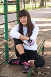Sports girl relaxing after training. Outdoor portrait of young pretty sporty woman wearing leggings, hoodie, sport gloves, trainers with pink laces, sitting on Royalty Free Stock Images