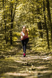 Sports girl runs on a footpath in the woods Royalty Free Stock Image