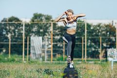 Sports girl runs and jumps over obstacles Royalty Free Stock Images