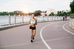 Sports girl runs in park and listening to music Royalty Free Stock Photography