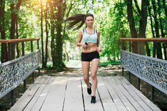 Sports girl runs in park and listening to music Royalty Free Stock Images