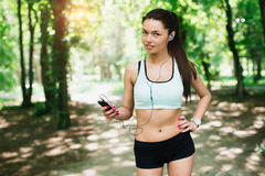 Sports girl runs in park and listening to music Royalty Free Stock Photo